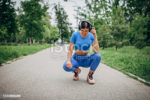 One young fit woman in sports clothing kneeling in public park and listening music on headphones.