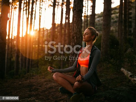 istock Woman in sports clothing meditating in a forest at sunrise 516658556