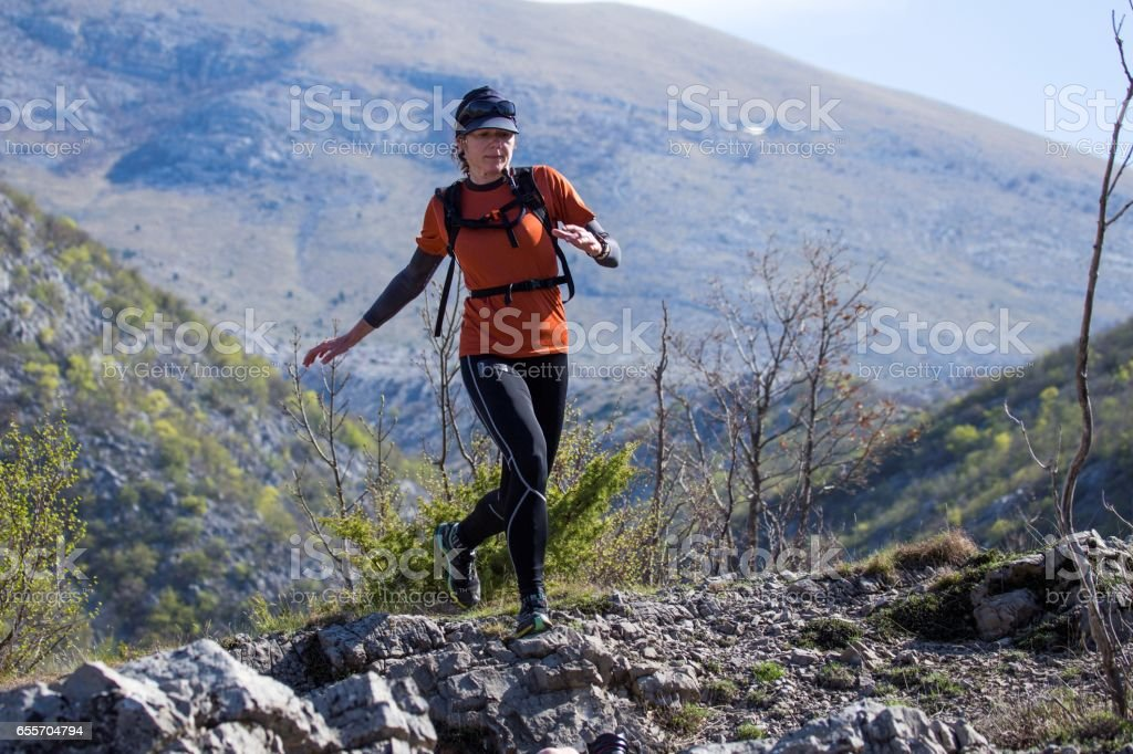 A woman in sports clothing running through the rocky mountains. National park Paklenica, the part of Velebit; the largest mountain range in Croatia. stock photo
