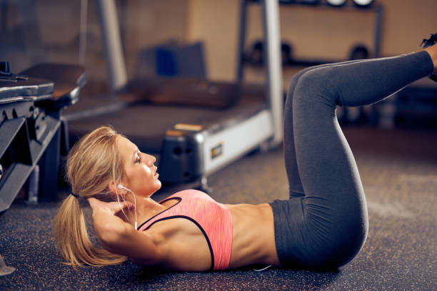 Woman in sportswear doing abs on the gym floor. Young sporty Caucasian  blonde woman in sportswear doing abs on the gym floor. Healthy lifestyle concept. abdominal muscle stock pictures, royalty-free photos & images