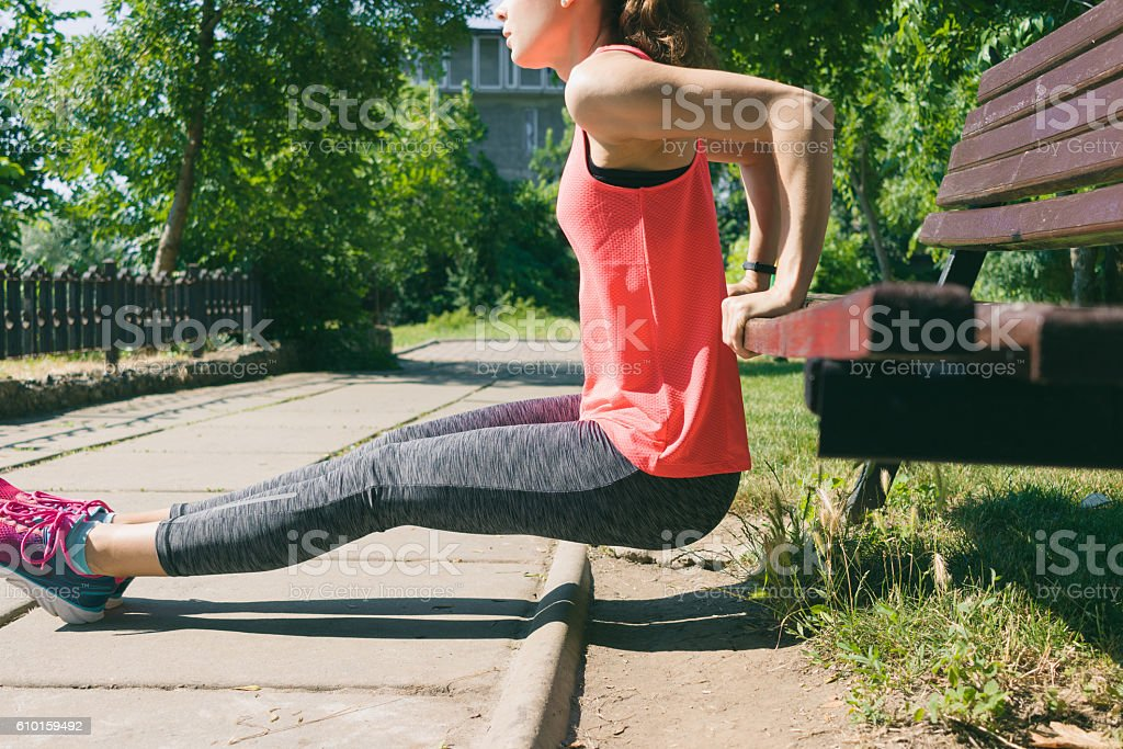Woman in sportswear doing exercise on triceps on a bench stock photo