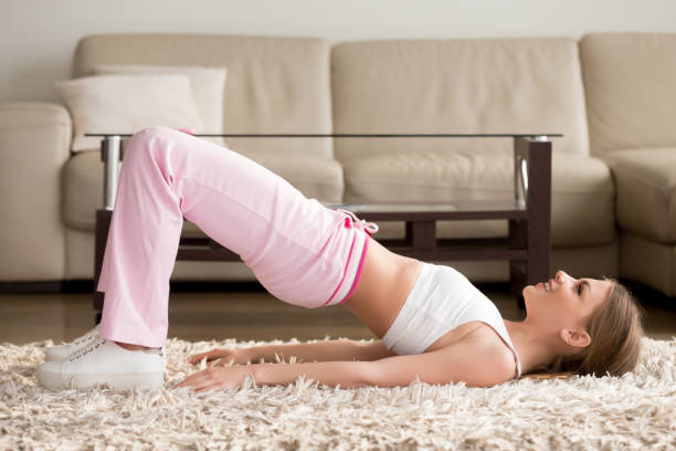 Woman in sportswear doing hip bridge exercise – zdjęcie
