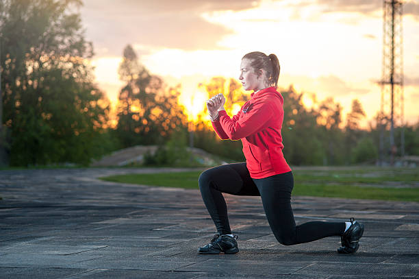 woman in sportswear doing squats outdoors - lunge stock photos and pictures