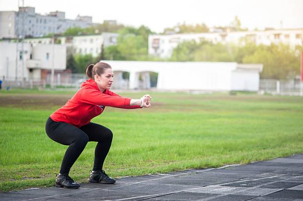 Mujer en ropa deportiva haciendo se pone en cuclillas al aire libre - foto de stock