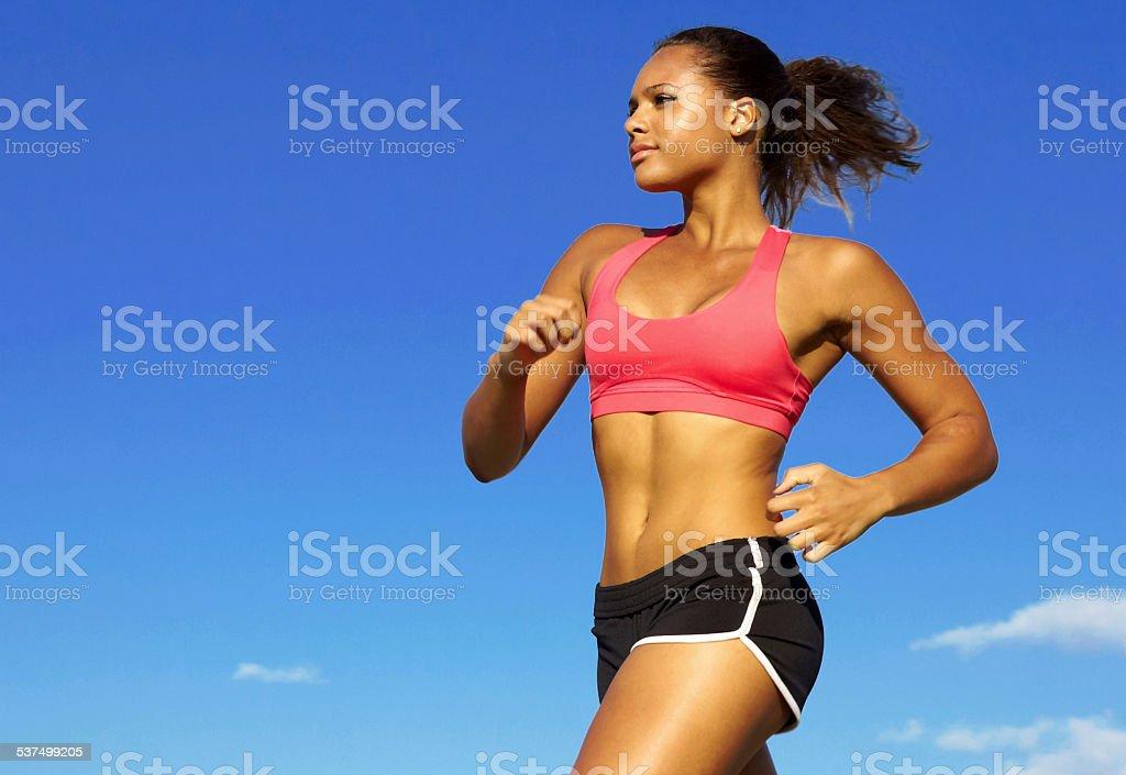 Woman In Sportswear Jogging Against Blue Sky stock photo