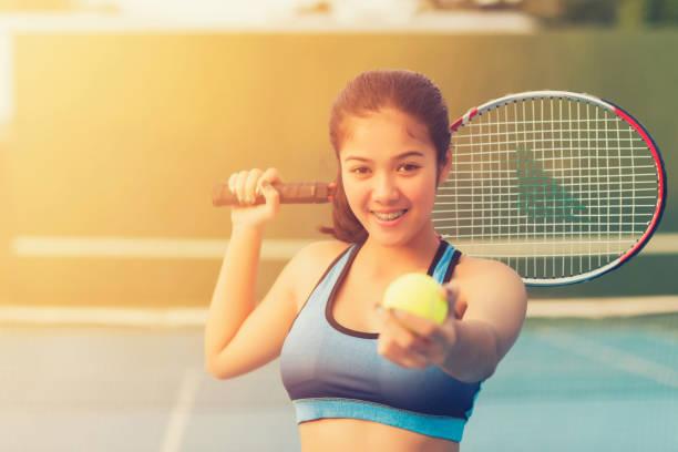 Frau in der Sportswear dient Tennisball. – Foto