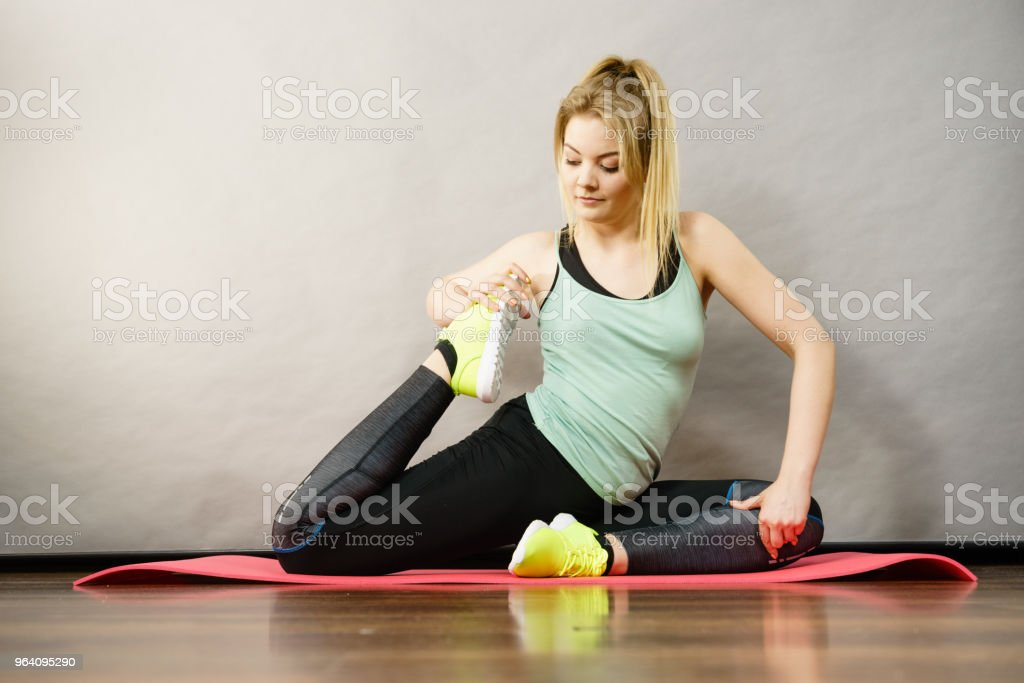 Woman in sportswear stretching legs - Royalty-free Adult Stock Photo