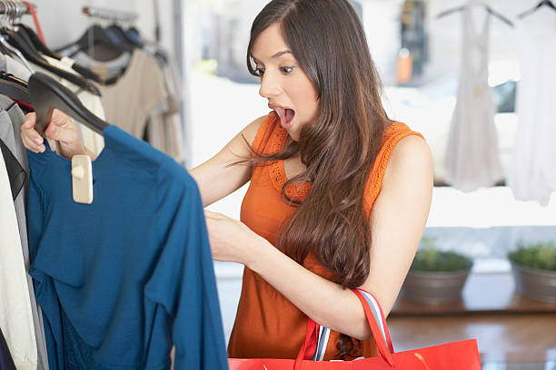 Woman in store looking at a shirt in shock stock photo