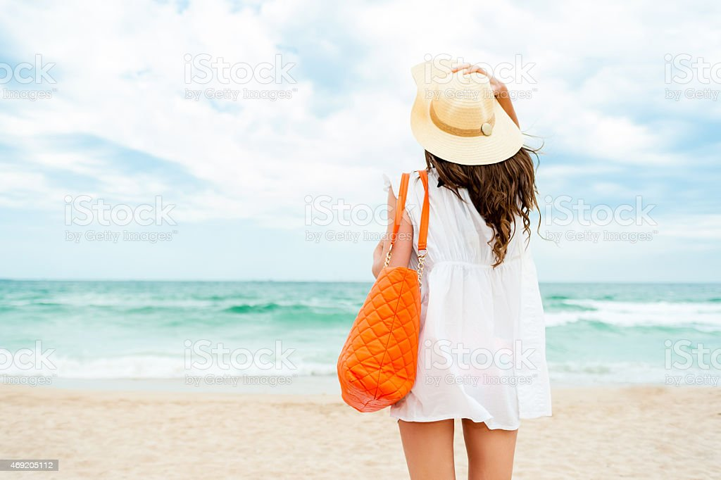 Woman in straw hat at sea stock photo