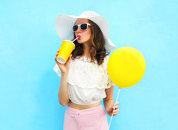 woman in straw hat with balloon drinks fruit juice cup - sommermode stock-fotos und bilder