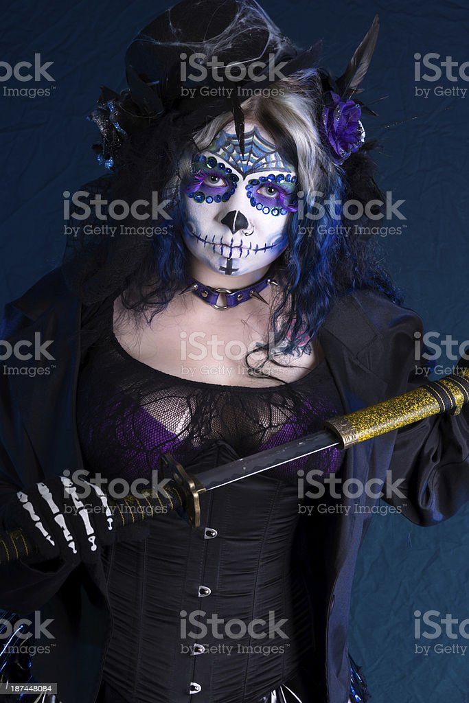 Woman in sugarskull makeup drawing sword. royalty-free stock photo