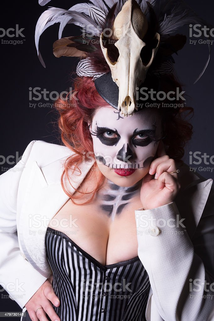 Woman in sugarskull makeup looking at camera while touching face. stock photo