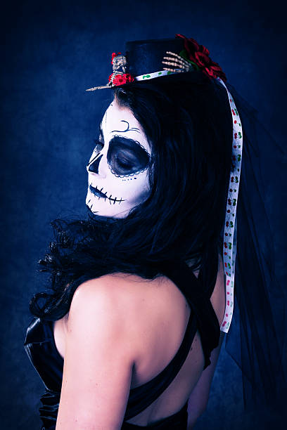 Woman in SugarSkull makeup, profile waist up with hair clip. stock photo