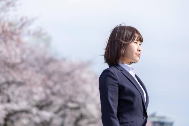 女性のスーツとチェリーブロッサム - 女性 横顔 日本人 ストックフォトと画像