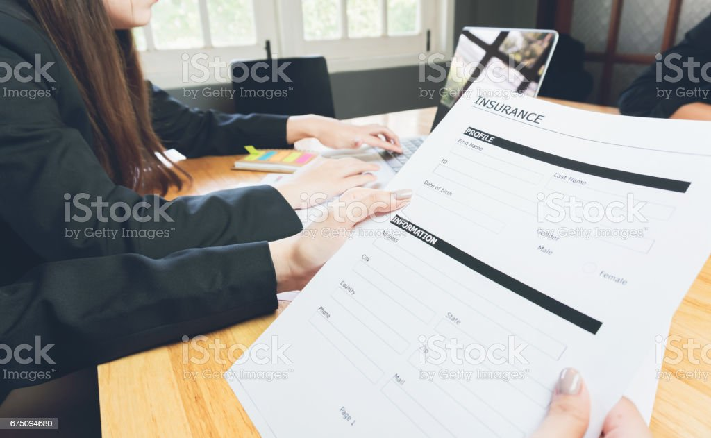 woman in suit in office showing an insurance policy, Concept fill their laptop to get online. stock photo