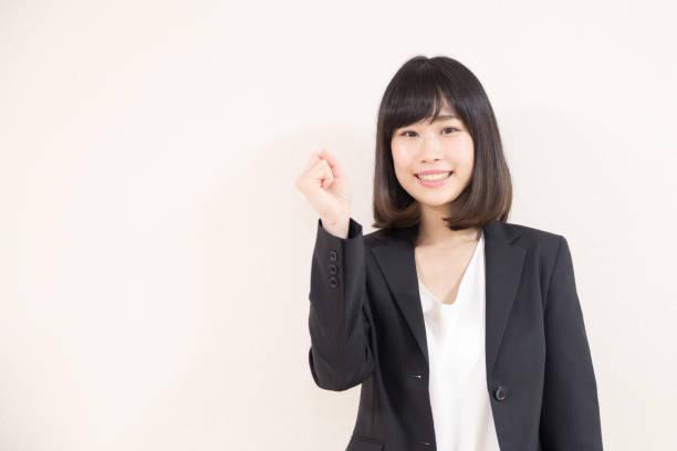 ガッツポーズするスーツの女性 - kurze schwarze haare stock-fotos und bilder