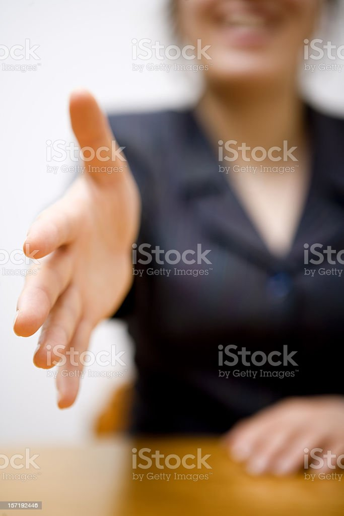 Woman in suit stretching out arm for a handshake royalty-free stock photo