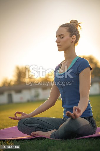 Attractive sporty woman having her outdoor training on sunny autumn day in park and soccer pitch. Young woman is yoga fan and living healthy life.