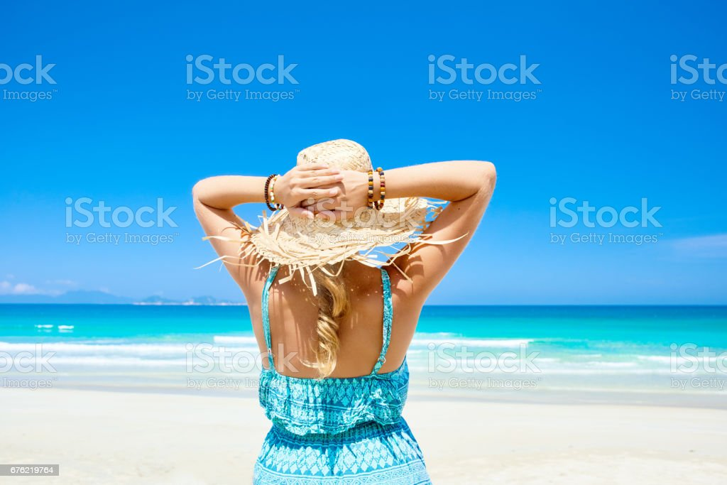 Woman in summer dress and straw hat on beach looking beatiful sea and islands stock photo