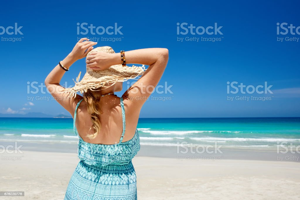 Woman in summer dress and straw hat on beach looking beatiful sea. stock photo