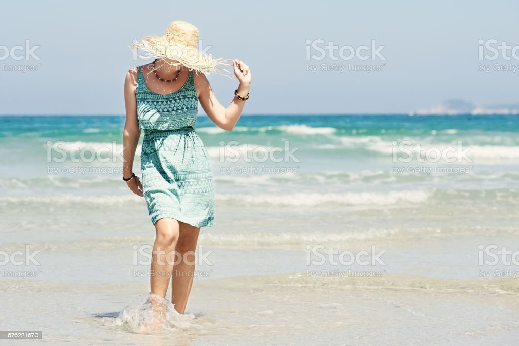 Woman in summer dress and straw hat walking on beach. stock photo