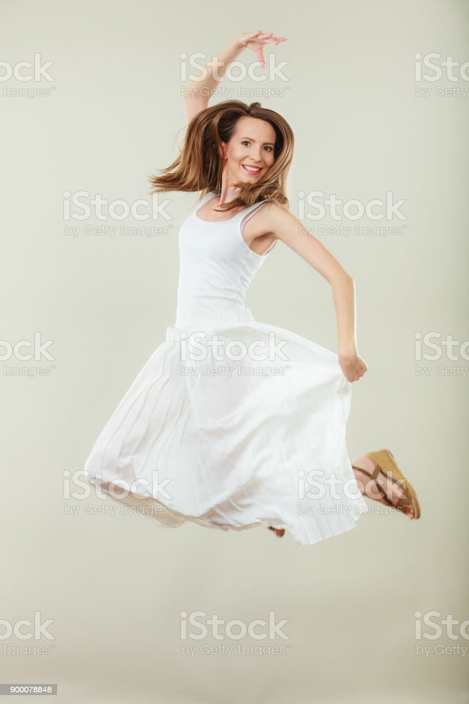 Woman in summer white dress jumping - foto stock