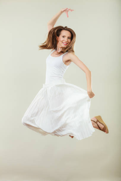 Woman in summer white dress jumping stock photo