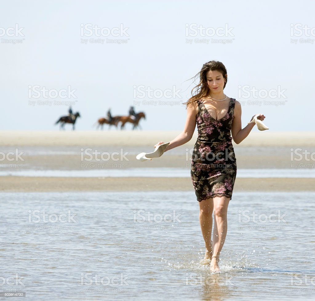 Woman in sundress walking barefooted through tidal pool stock photo