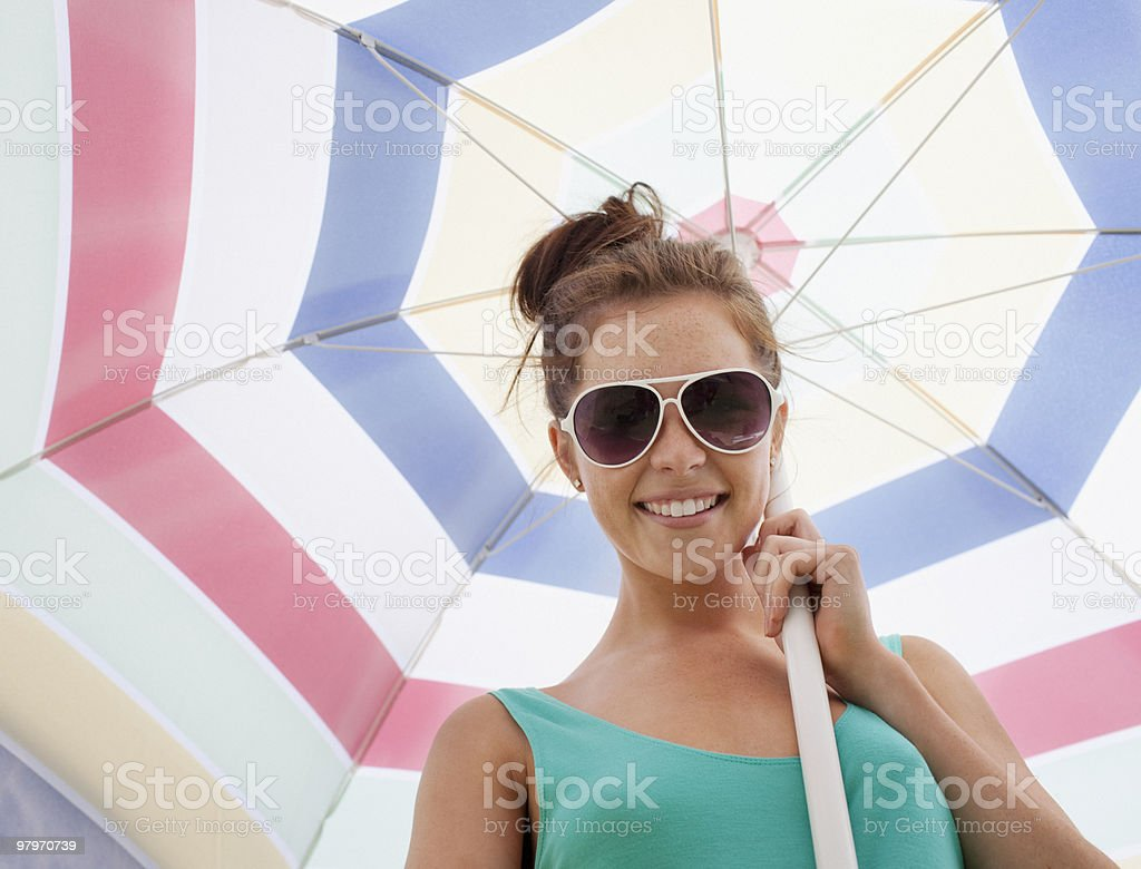 Woman in sunglasses holding beach umbrella royalty-free stock photo