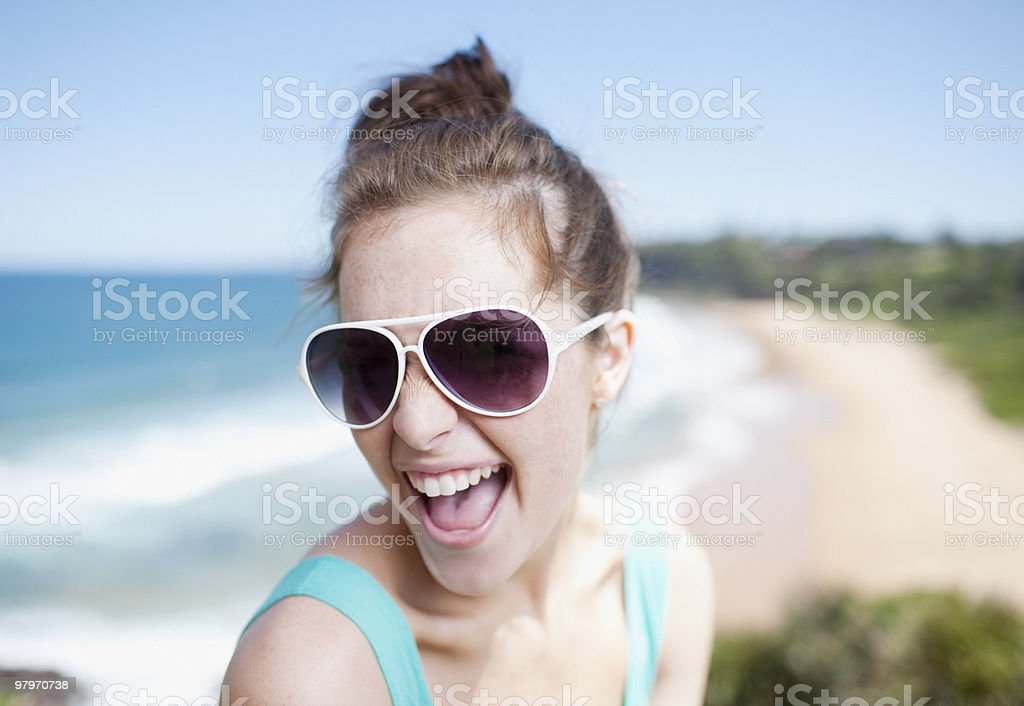 Woman in sunglasses laughing with ocean in background royalty-free stock photo