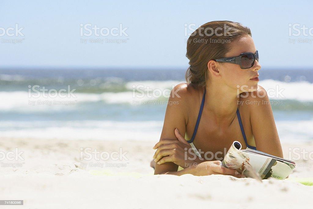 Mulher com óculos de sol deitado na praia com Revista foto de stock royalty-free