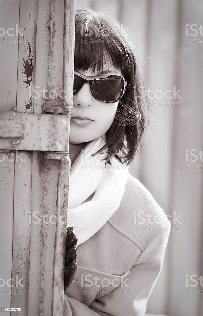 Woman in sunglasses peers out from behind a fence royalty-free stock photo