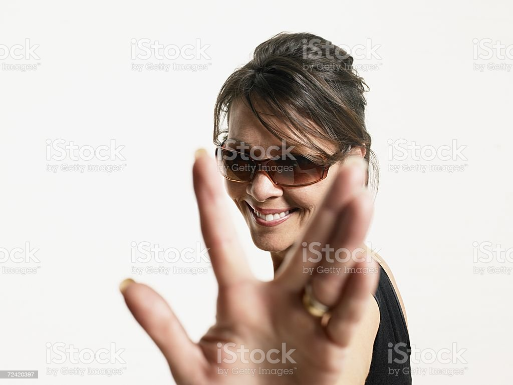 Woman in sunglasses reaching out royalty-free stock photo