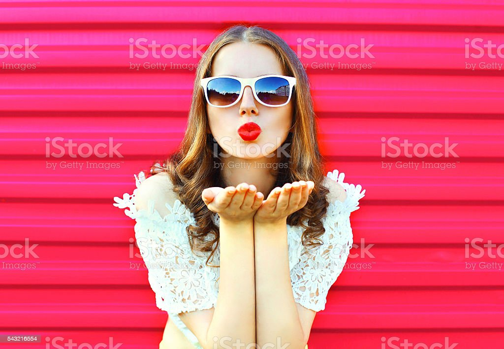 Woman in sunglasses sends an air kiss over colorful pink stock photo