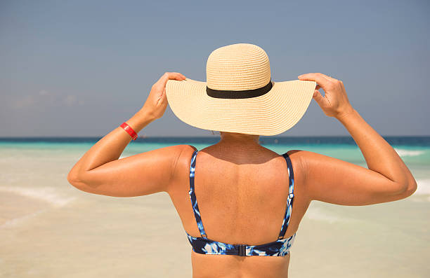 Woman in sunhat on the beach Woman in sunhat on the beach Zanzibar middle aged women in bikinis stock pictures, royalty-free photos & images