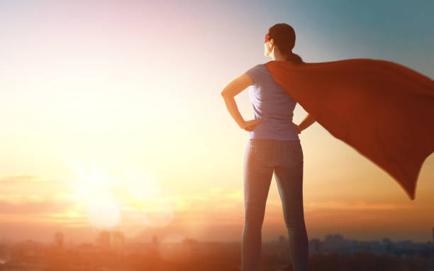 woman in superhero costume Joyful beautiful young woman in superhero costume posing on sunset background. hope concept stock pictures, royalty-free photos & images