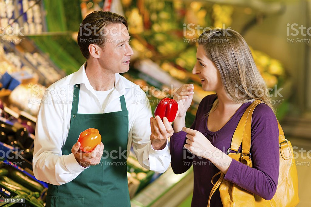 Woman in supermarket and shop assistant stock photo