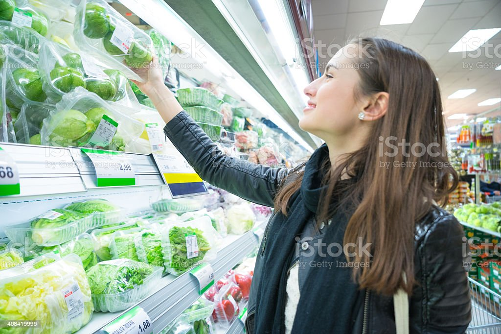 Woman In Supermarket At Vegetable Shelf Shopping stock photo