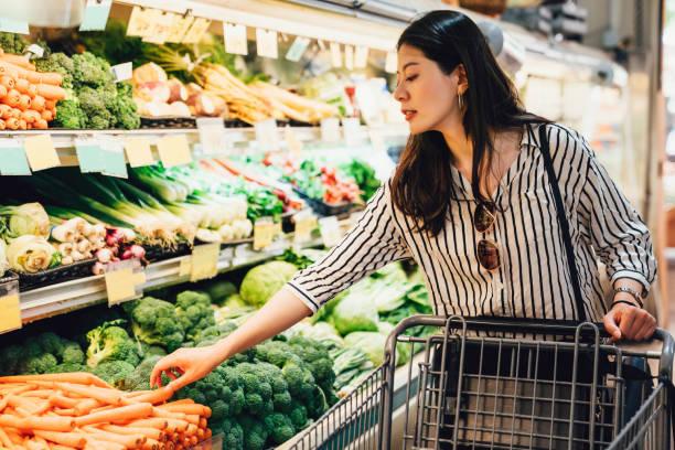 woman in supermarket pushing shopping cart stock photo