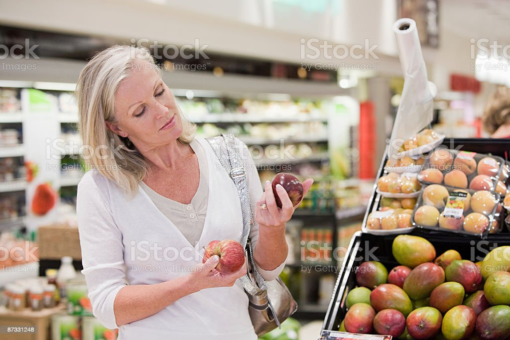 Woman in supermarket with apples royalty-free stock photo