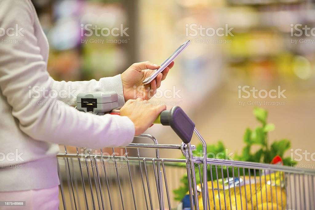 Woman in supermarket with mobile phone and trolley stock photo