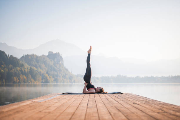 Woman in Supported Shoulder Stand Overlooking Lake Bled stock photo