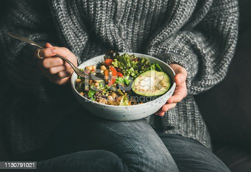 Healthy vegetarian dinner. Woman in grey jeans and sweater eating fresh salad, avocado half, grains, beans, roasted vegetables from Buddha bowl. Superfood, clean eating, dieting food concept
