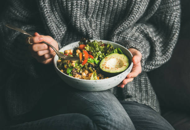 woman in sweater eating fresh salad, avocado, beans and vegetables - healthy food imagens e fotografias de stock