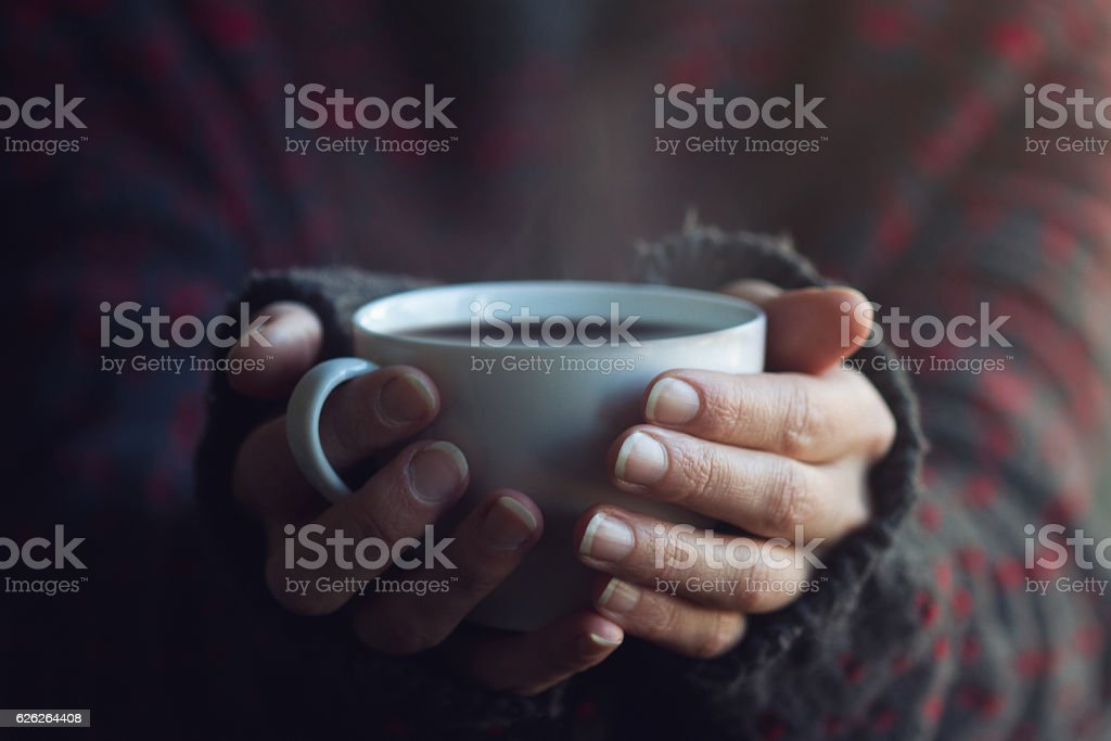 Woman in sweater hands holding a cup of warm coffee stock photo