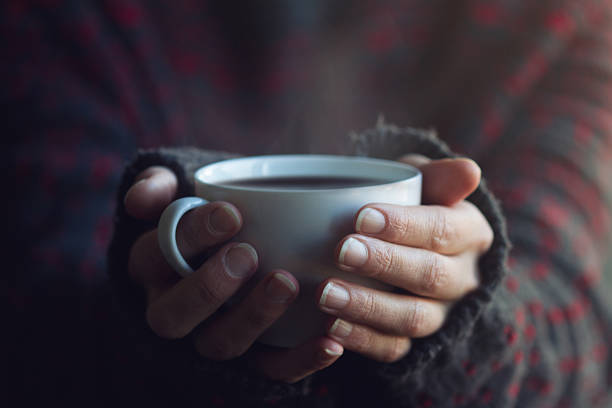woman in sweater hands holding a cup of warm coffee - heißes wasser trinken stock-fotos und bilder