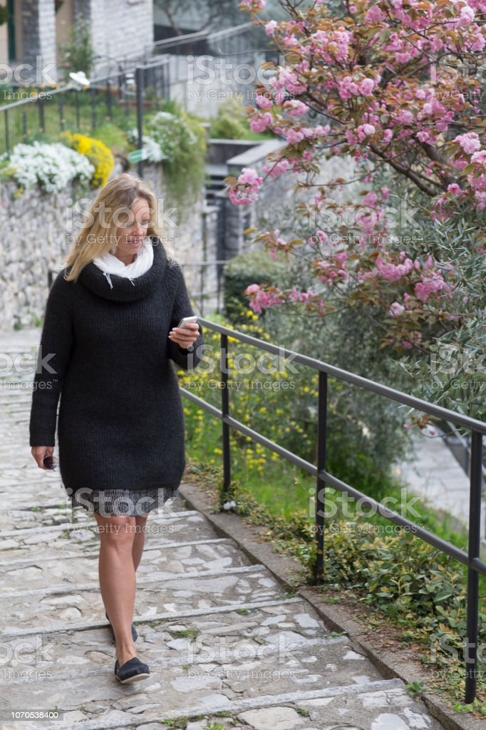 She is walking up cobblestone path by shrubs in blossom