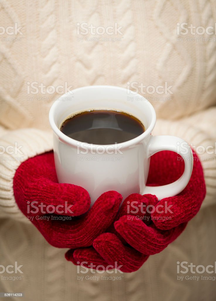 Woman in Sweater with Red Mittens Holding Cup of Coffee stock photo