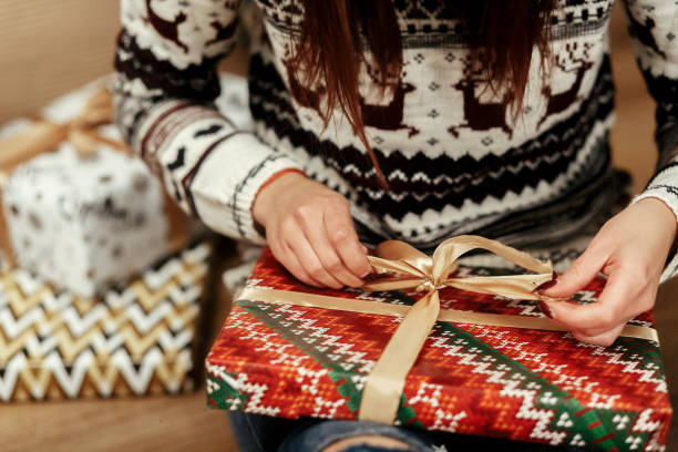 woman in sweaters with deers openning christmas presents under tree closeup. stylish gift ideas. seasonal greetings concept. joyful moment. space for text - avvolto foto e immagini stock
