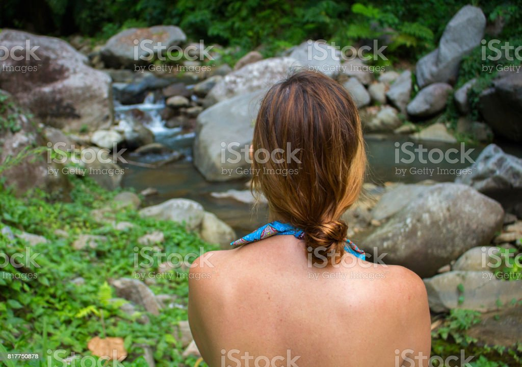 Woman in swimsuit looks at the river in stone riverbed, rocks and greenery of tropical forest. stock photo